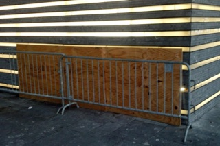 Cheap plywood covers the hole in the outside structure of the Famine memorial and a metal barrier stands in front.